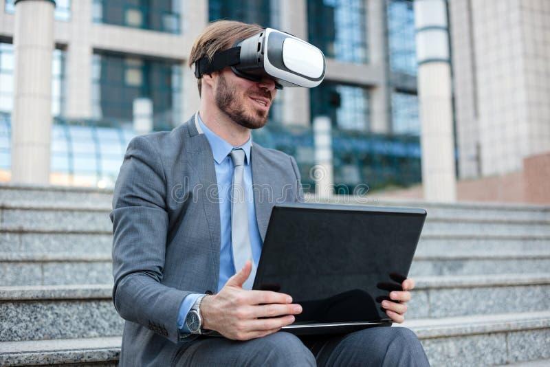使用虚拟现实模拟器风镜的成功的年轻商人和研究在办公楼前面的一台膝上型计算机 库存图片