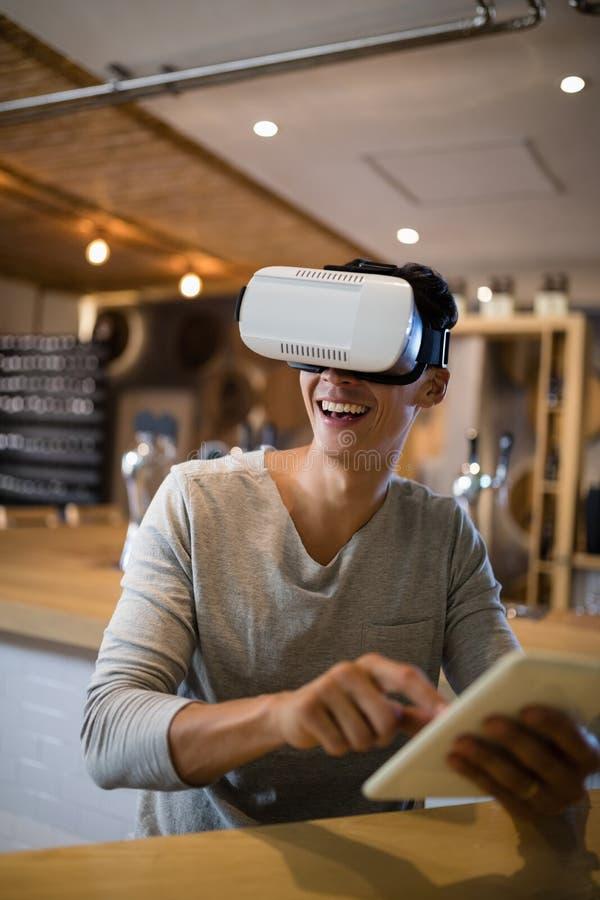 使用虚拟现实耳机和数字式片剂的人在餐馆 图库摄影