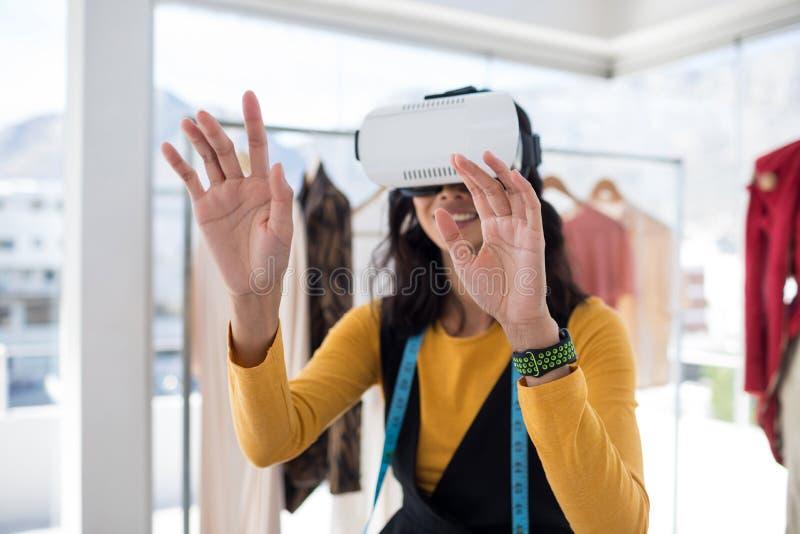 使用虚拟现实耳机的女性设计师 免版税图库摄影