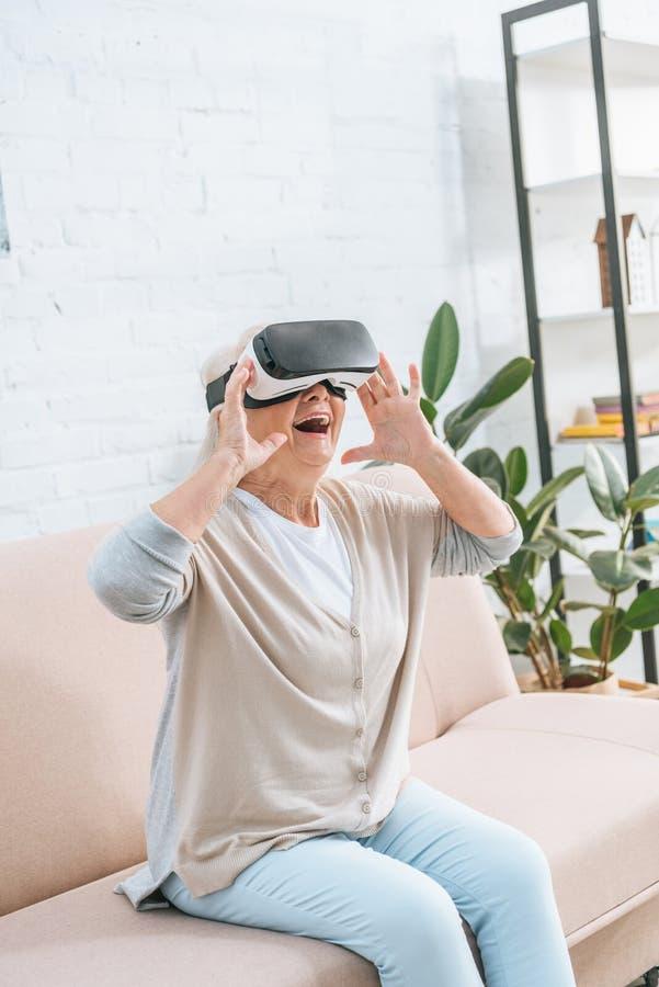 使用虚拟现实耳机的激动的资深妇女 免版税库存图片