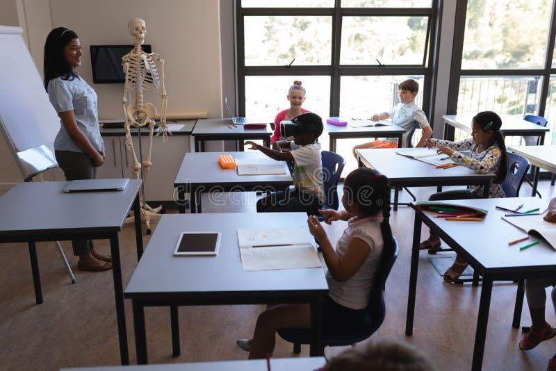 使用虚拟现实耳机的男小学生和他的看他的同学和老师 免版税图库摄影