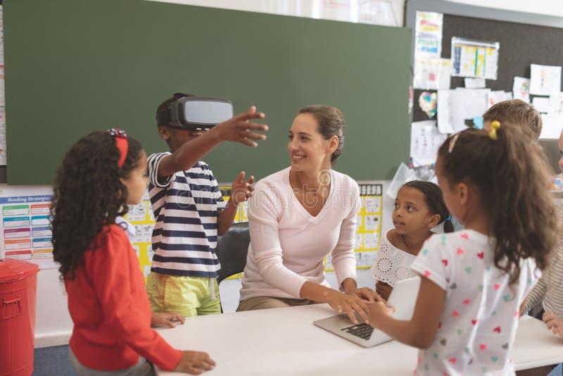 使用虚拟现实耳机的男小学生在学校在有他的同学和她的老师的n教室 免版税图库摄影