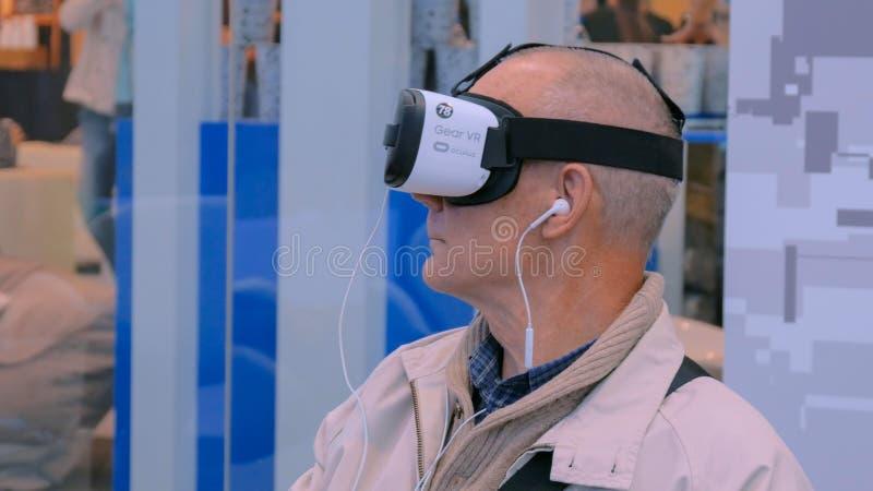 使用虚拟现实耳机的老人 免版税库存图片