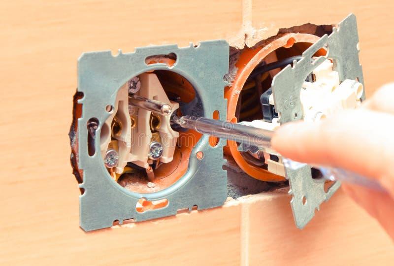 使用螺丝刀的电工和安装电源插座 库存图片