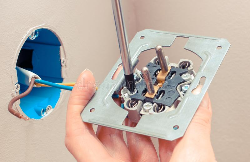 使用螺丝刀的电工和安装电源插座 免版税库存图片