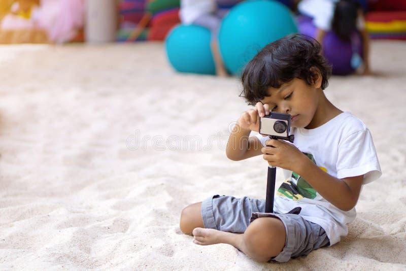 使用行动照相机的亚裔男孩采取图片或录影 图库摄影