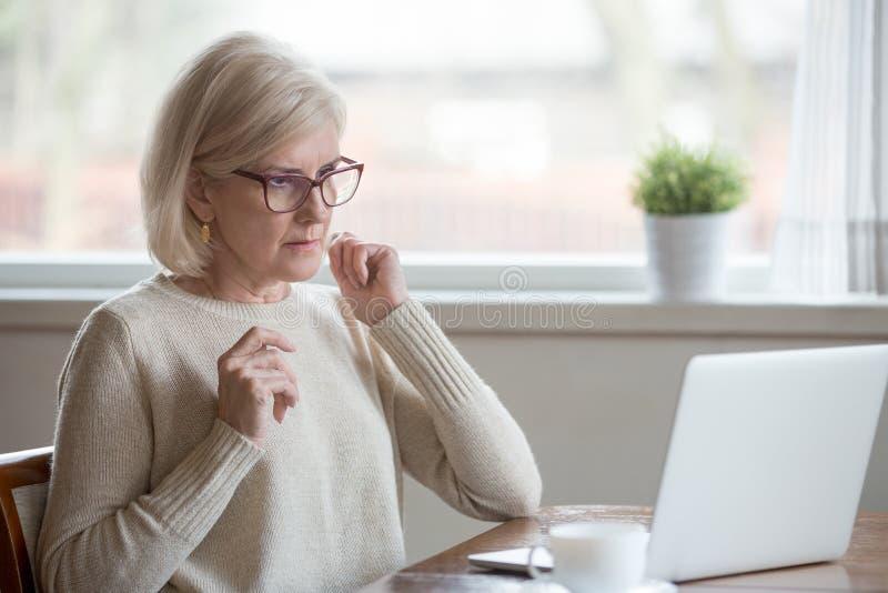 使用被混淆的膝上型计算机的年迈的妇女看错误信息 免版税库存照片