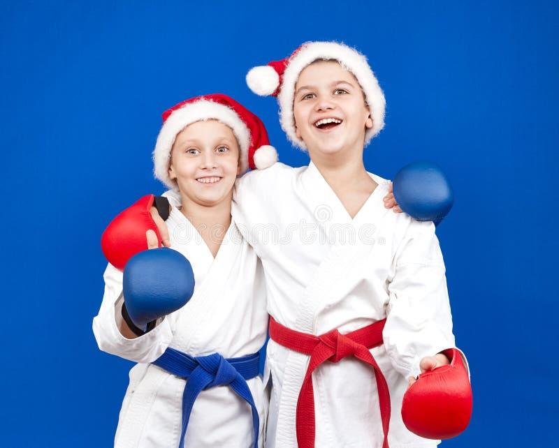 使用覆盖物在他们的手上和在帽子圣诞老人的运动员微笑着 库存图片