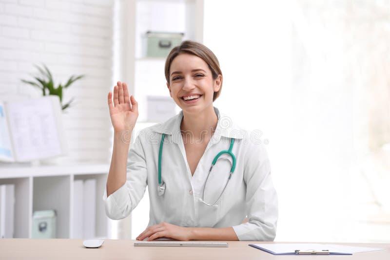 使用视频聊天的女性医生在工作场所 库存图片