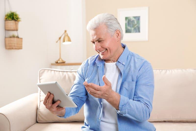 使用视频聊天的成熟人在片剂 图库摄影
