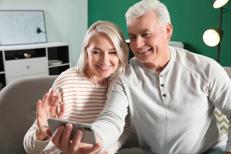 使用视频聊天的成熟夫妇在手机 免版税库存照片