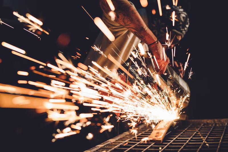 使用角度研磨机的工作者在工厂和投掷的火花 库存照片