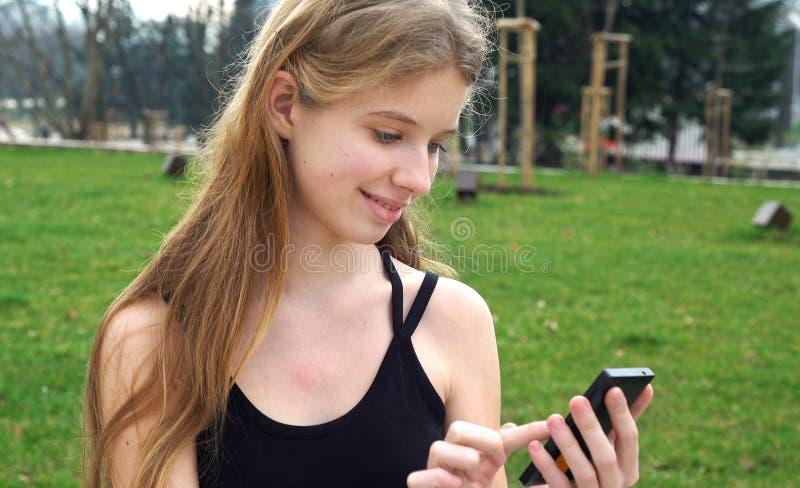 使用触摸屏幕电话的妇女户外在城市公园 免版税图库摄影