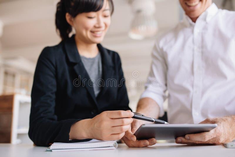 使用触摸屏幕计算机的买卖人在办公室 库存图片