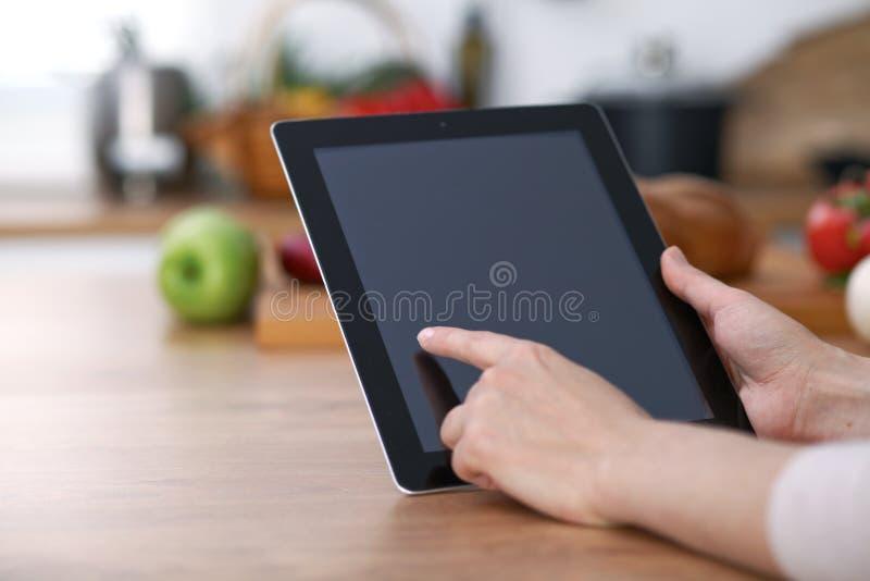 使用触摸板的Haman手在厨房里 做网上购物的妇女特写镜头乘片剂计算机和信用汽车 免版税库存图片