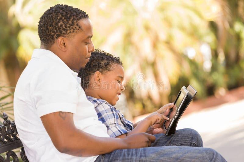 使用触摸板计算机片剂的混合的族种父亲和儿子 库存照片