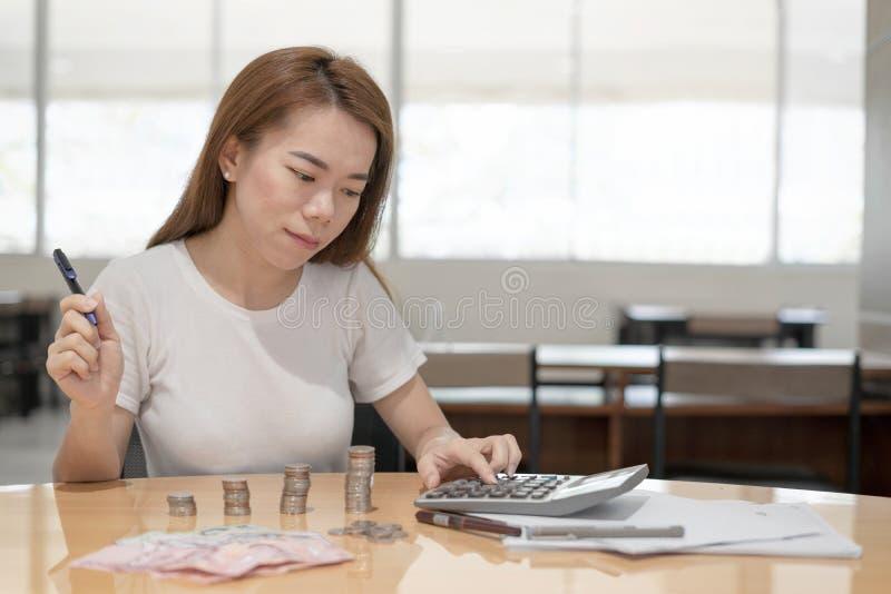 使用计算器的亚裔女商人在有金钱的书桌上和硬币在办公室背景中 免版税库存图片