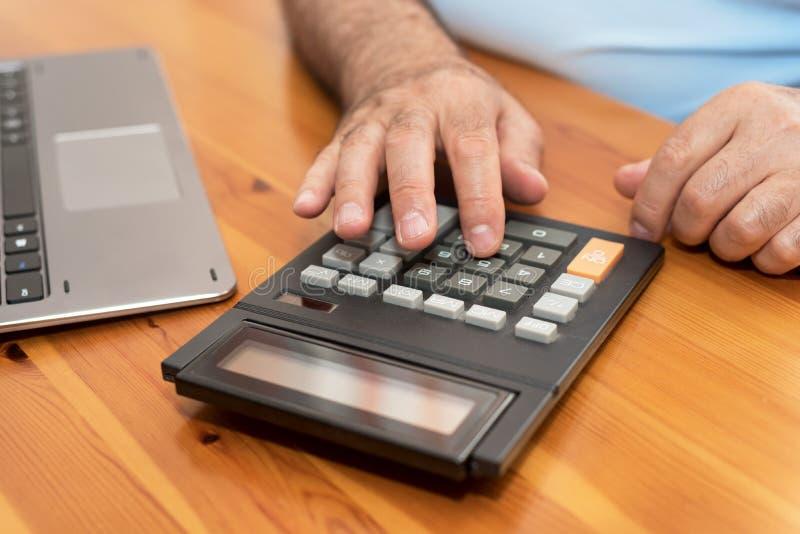 使用计算器的人,在家计算票据 免版税库存照片