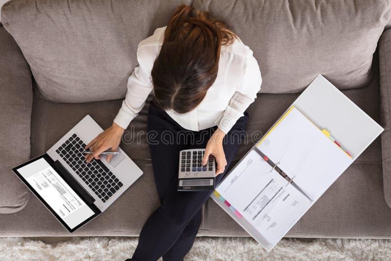 使用计算器的会计妇女计算的财务发货票 免版税库存图片