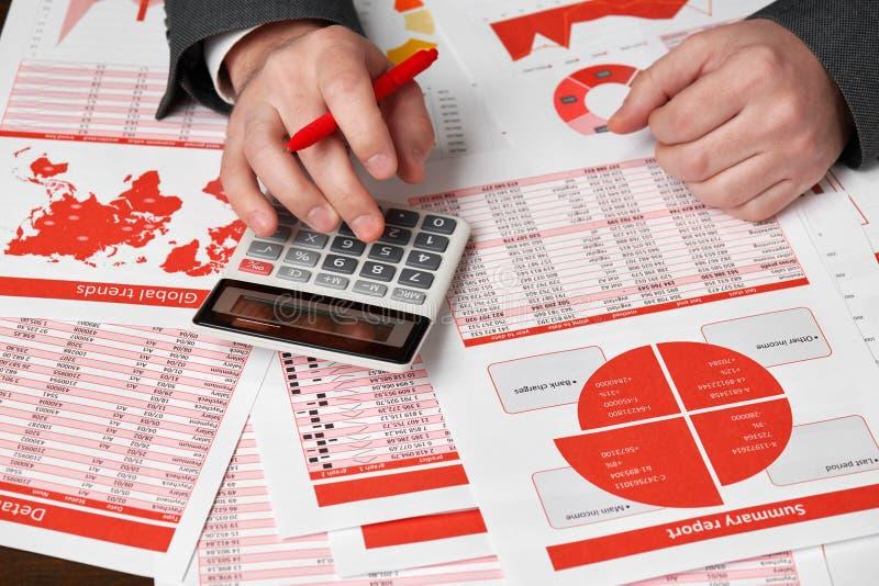 使用计算器的商人会计为计算在书桌办公室的财务 企业财务会计概念红色报告 库存照片