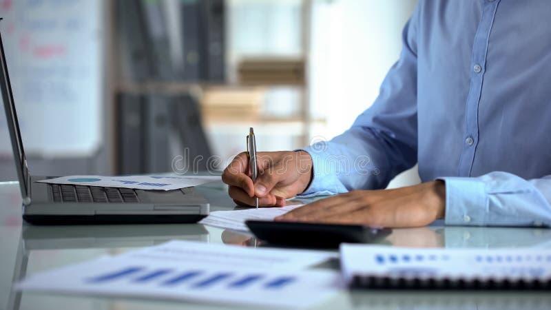 使用计算器的商人会计和填装报告靠近膝上型计算机在办公室 免版税库存照片