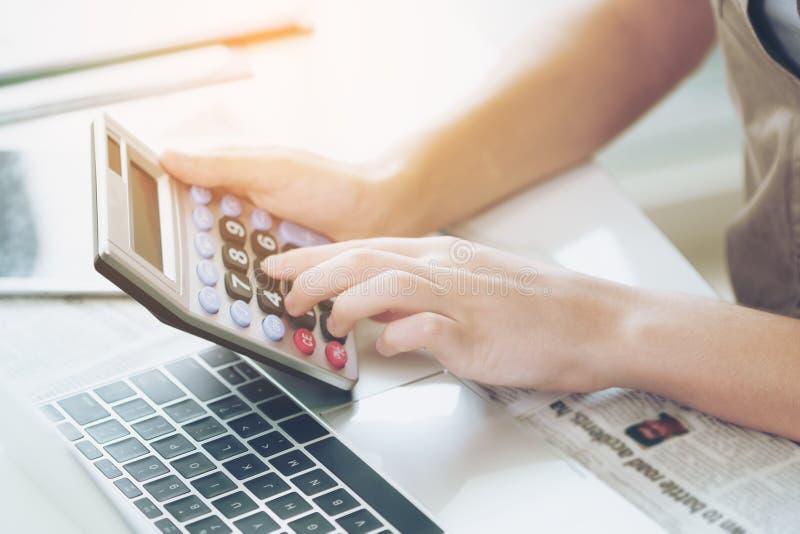 使用计算器的女商人在办公室 图库摄影