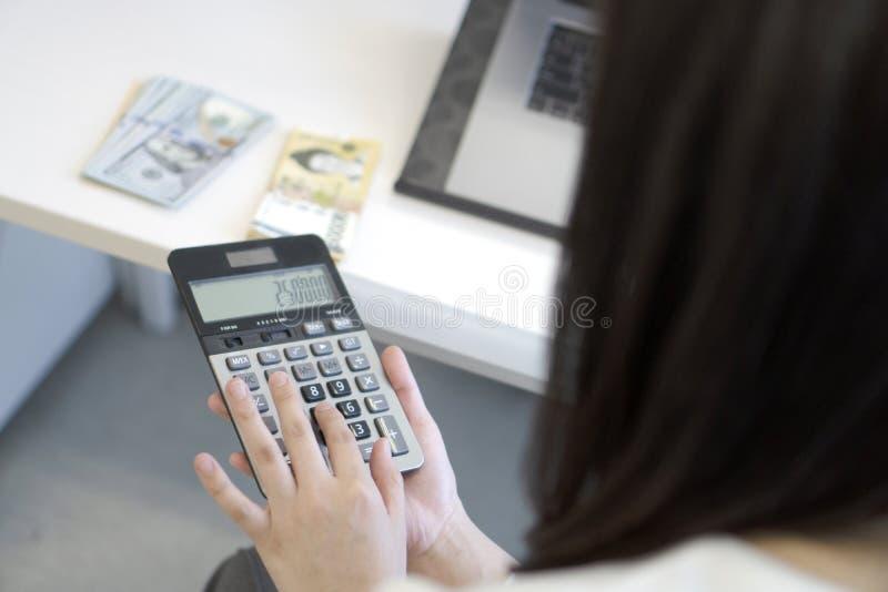 使用计算器的女商人在办公室 免版税库存照片