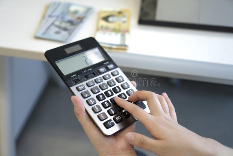 使用计算器的女商人在办公室 免版税库存图片