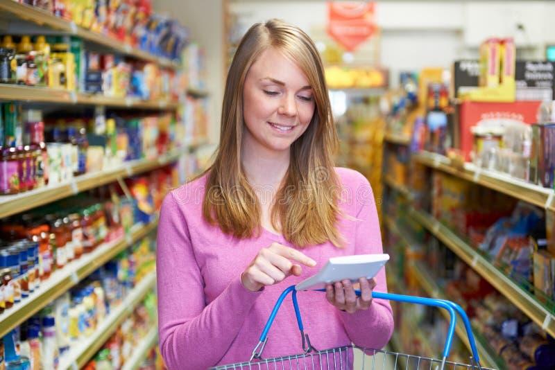 使用计算器的妇女,购物在超级市场 库存图片