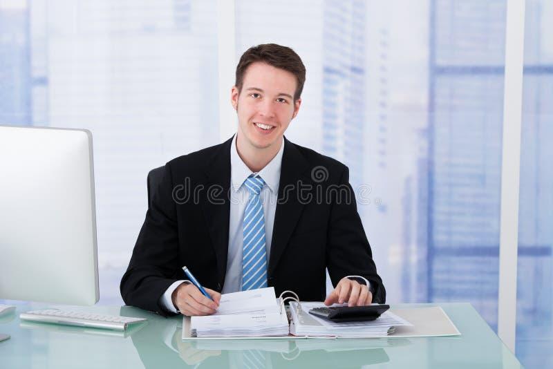 使用计算器的确信的商人在办公桌 库存照片
