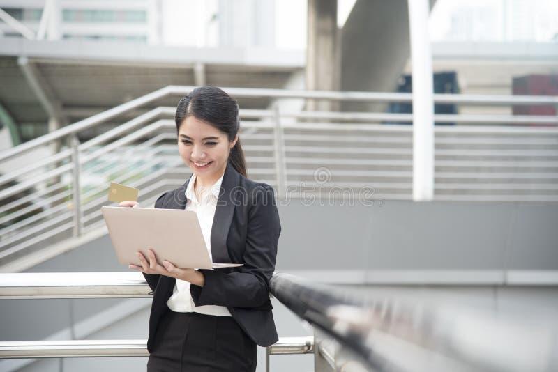 使用计算机和信用卡的女实业家为在网上购物 库存照片