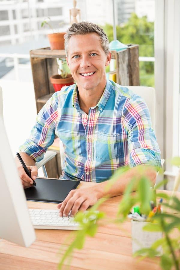 使用计算机和数字化器的微笑的偶然设计师 免版税图库摄影