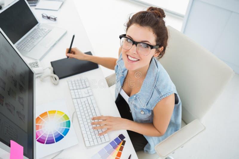 使用计算机和数字化器的微笑的设计师 免版税图库摄影