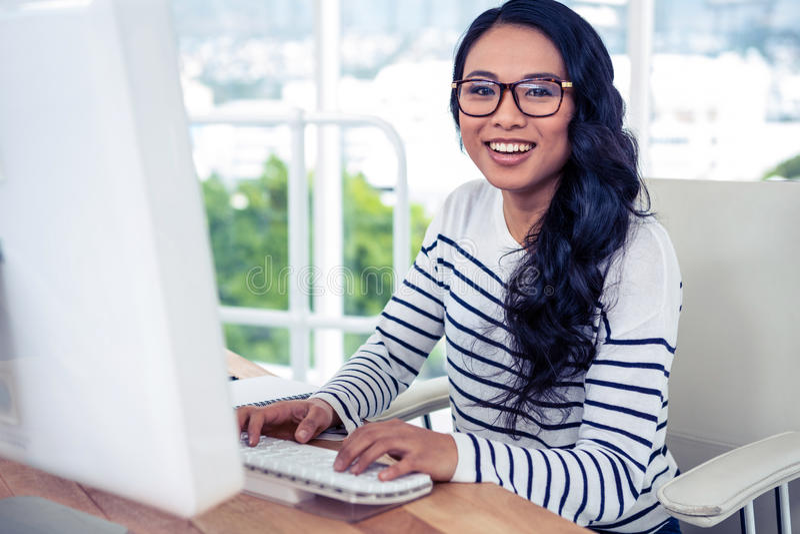 使用计算机和看的微笑的亚裔妇女照相机 免版税库存图片