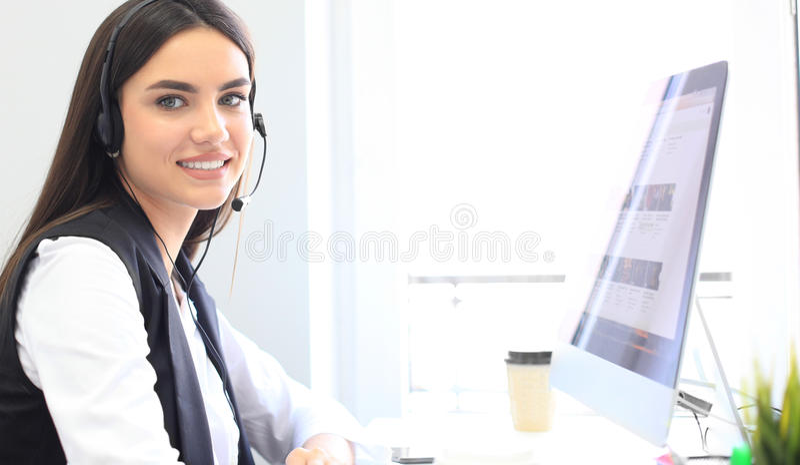 使用计算机在办公室-操作员,电话中心的女实业家佩带的话筒耳机 免版税图库摄影