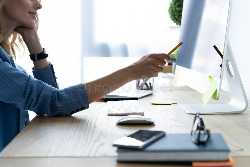 使用计算机的一名严肃的女实业家的画象在办公室 采取笔记的美丽的行家妇女在现代办公室 免版税库存图片