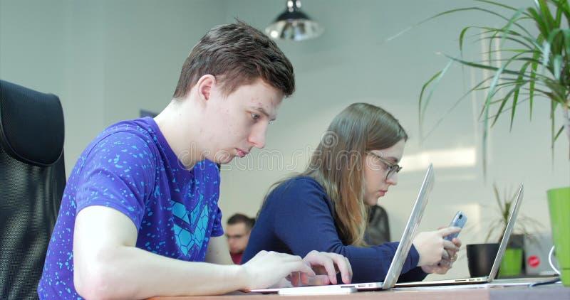 使用计算机的三个年轻商人在办公室 在创新的两个装饰员的同事 图库摄影