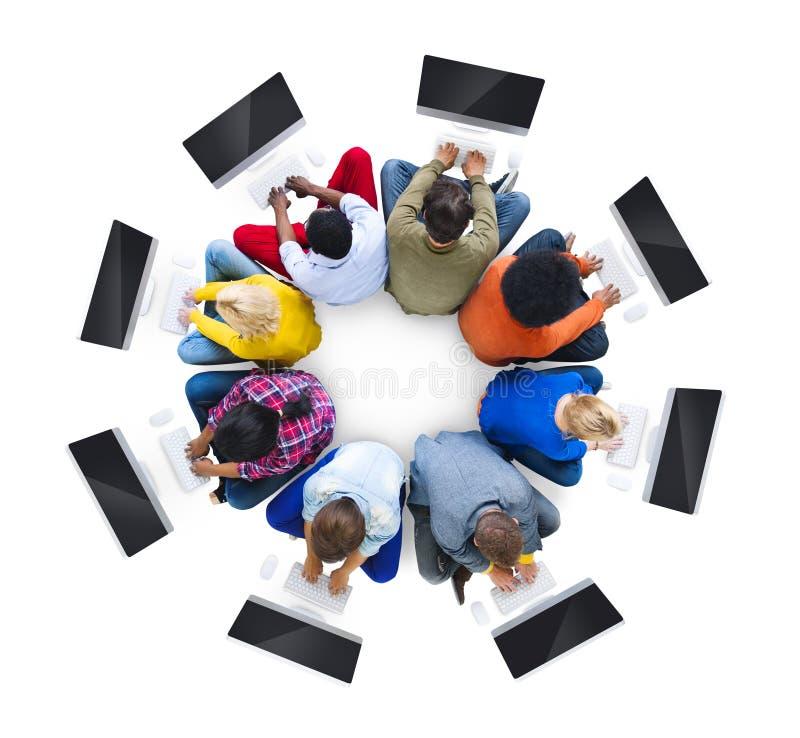使用计算机的不同种族的人民在一个圆位置 免版税图库摄影