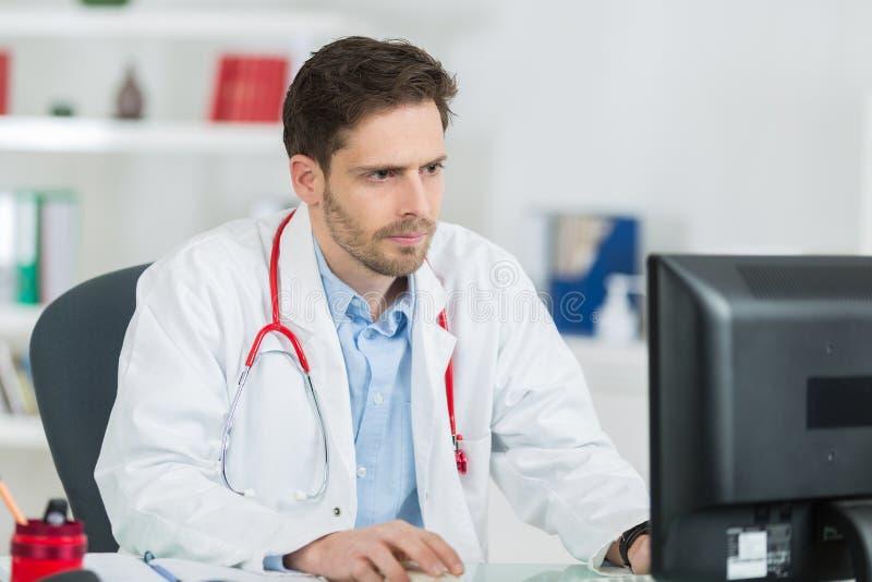 使用计算机的严肃的男性医生在医疗办公室 免版税库存照片