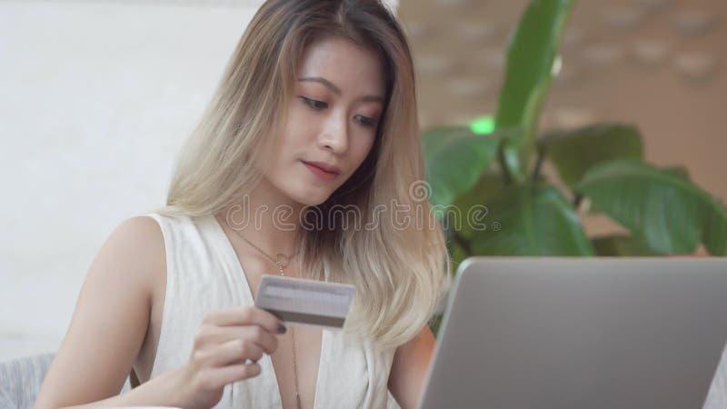 使用计算机的亚裔女孩为与信用卡的网上购买 库存图片