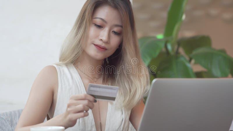 使用计算机的亚裔妇女为与信用卡的网上购买 库存照片