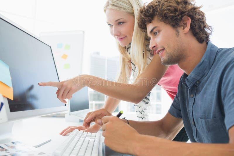 使用计算机的偶然夫妇在办公室 免版税库存照片
