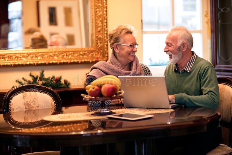 使用计算机的前辈微笑的愉快的夫妇在家 免版税库存图片