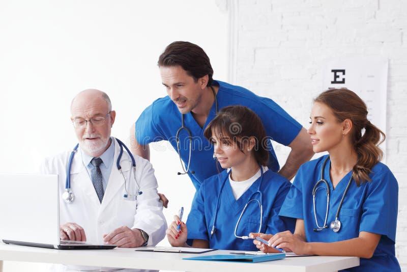 使用计算机的医生队 免版税库存图片