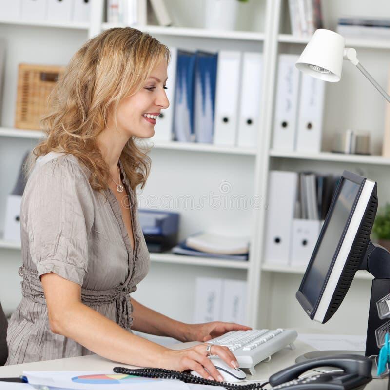 使用计算机的女实业家在书桌在办公室 库存照片