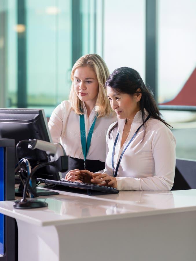 使用计算机的女性地勤人员在招待会在机场 免版税库存照片