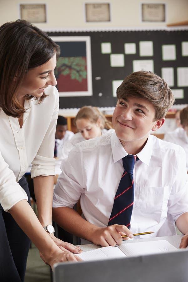 使用计算机的女老师帮助的学生在教室 免版税库存图片