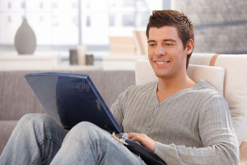 使用计算机的微笑的年轻人在扶手椅子 免版税图库摄影