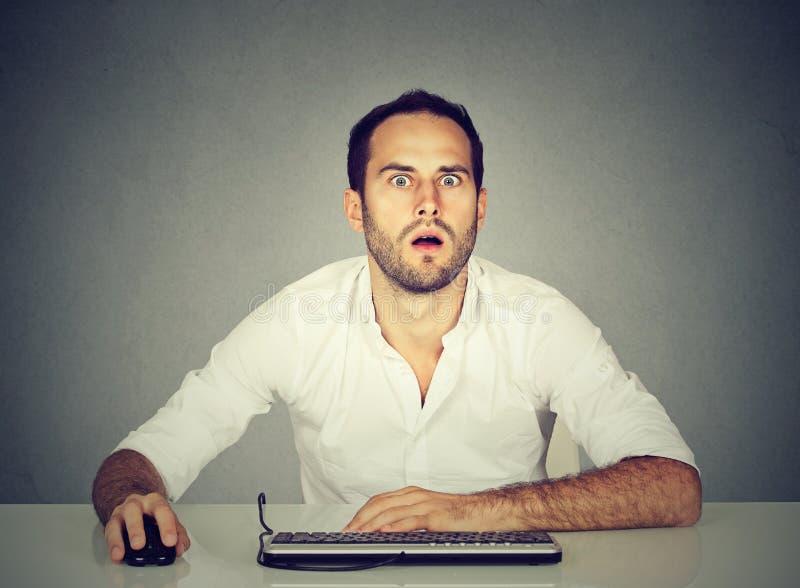 使用计算机的惊奇人在书桌 免版税库存照片