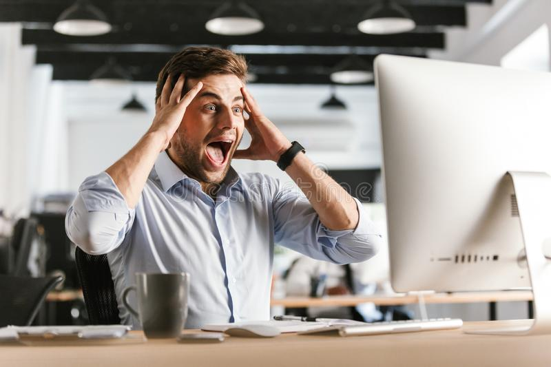 使用计算机的惊奇的叫喊的商人和拿着他的头 免版税图库摄影